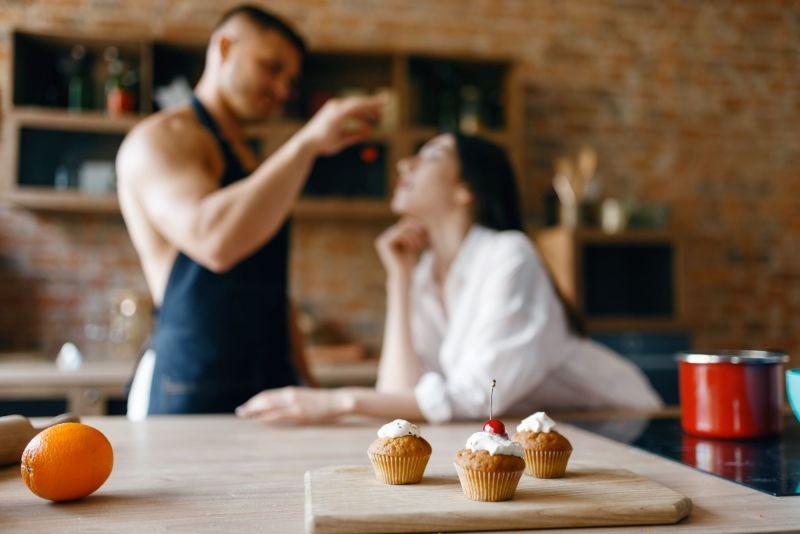 Man feeding woman in kitchen