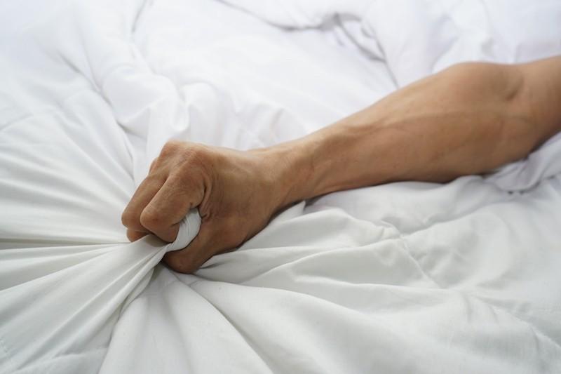 Man hand grabbing sheets