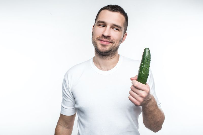 Man holding a cucumber