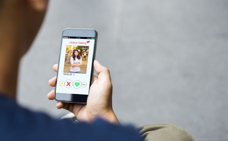 Man holding a phone screen showing a dating app