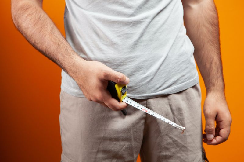 Man holding tape measure over crotch