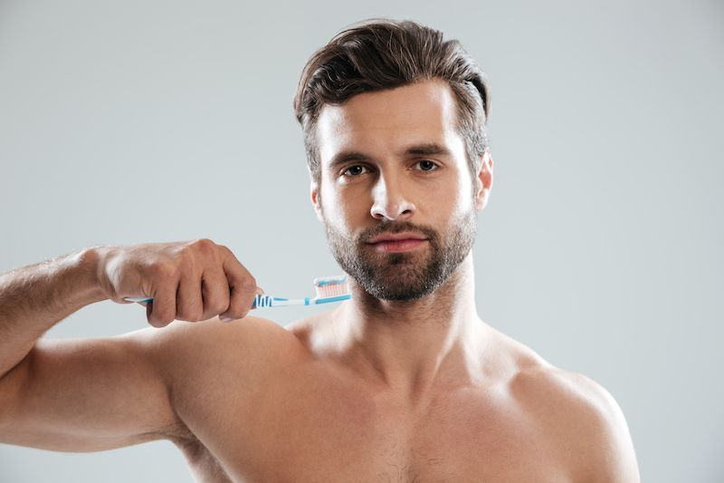 Man holding toothbrush to his face