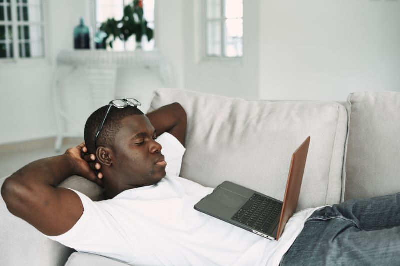 Man watching film at home on his laptop