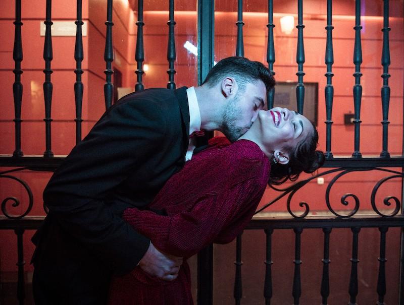 Man kissing women neck