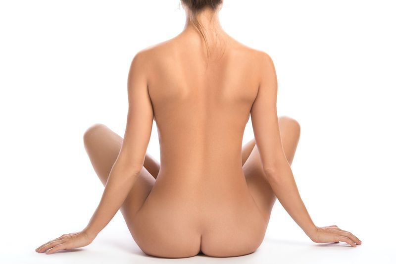 Nude woman's back sat cross legged