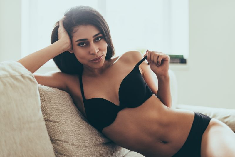 Playful woman removing bra on couch