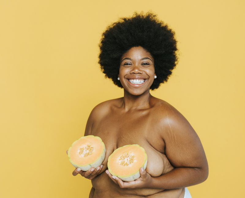 Smiling woman holding melon over breasts
