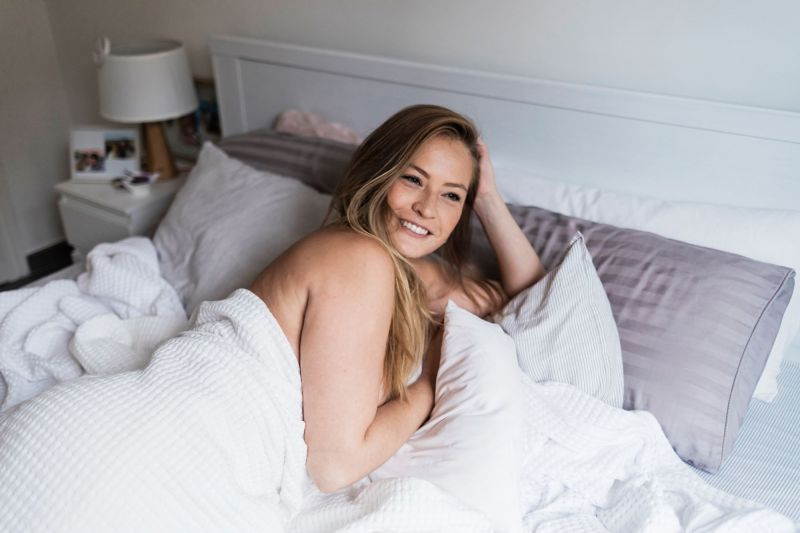 Smiling woman in bed in the morning