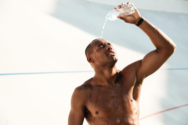 Man pouring water on himself