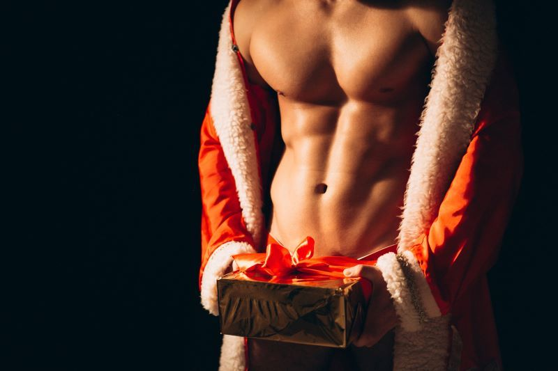 Topless man in Santa outfit holding present