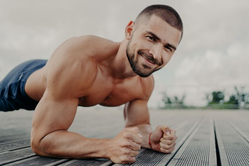Topless man smiling while exercising