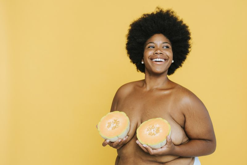 Topless smiling woman holding melon over breasts