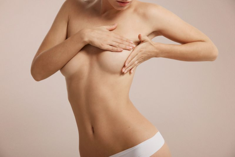 Topless woman checking breasts with hands