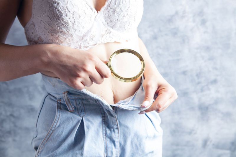 Woman examining crotch with magnifying glass