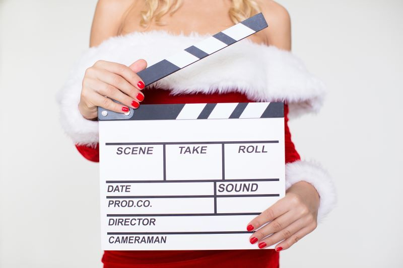 Woman holding clapper board in Santa outfit