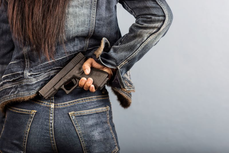 Woman holding gun behind her back