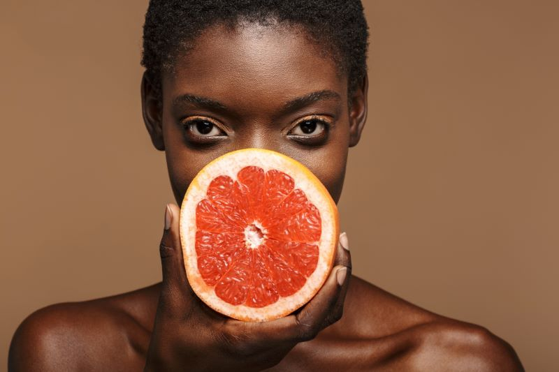 Woman holding half a grapefruit on brown background