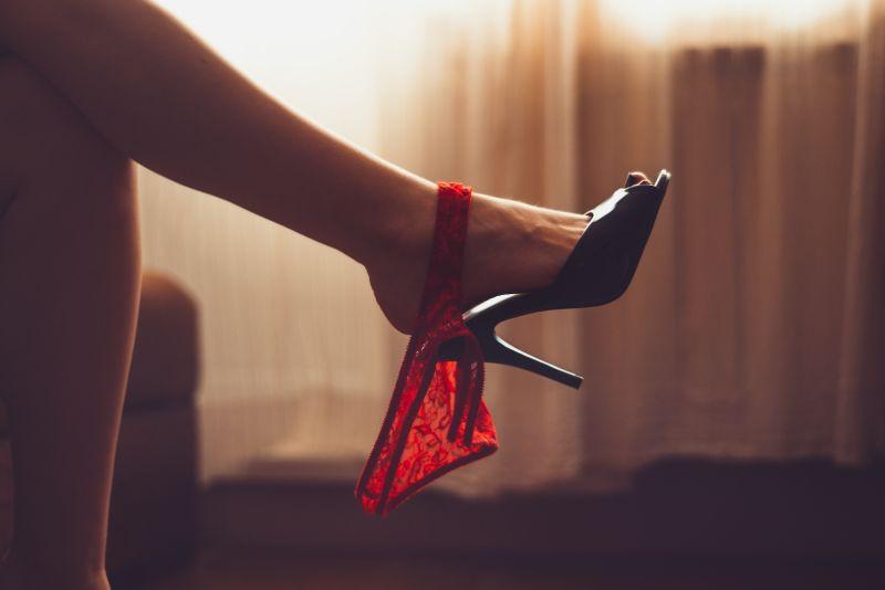 Woman's feet in black heels with panties hanging off