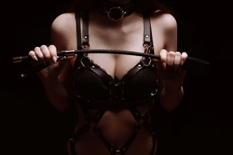 Woman in bondage gear holding whip