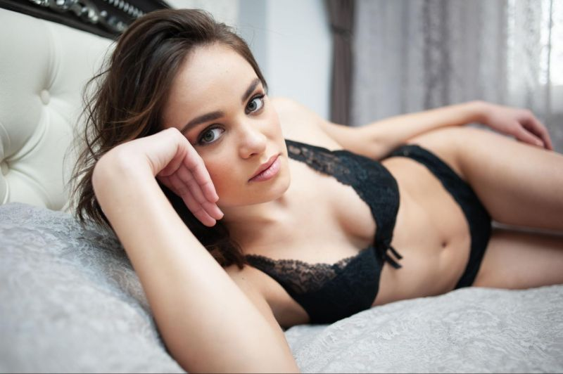 Woman in bed in lingerie looking at camera