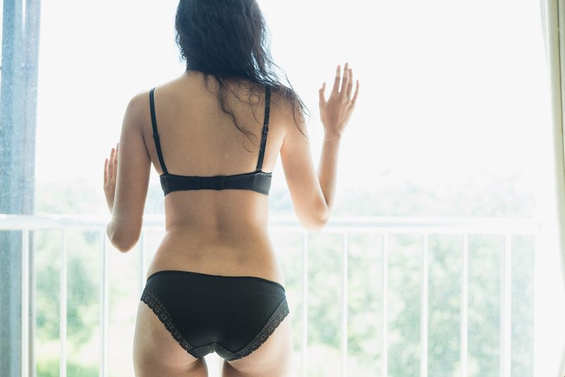Woman in lingerie leaning against a window looking out