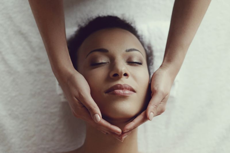 Woman lying down receiving face massage