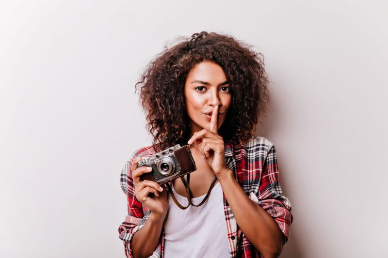 Woman making sh sign and holding camera