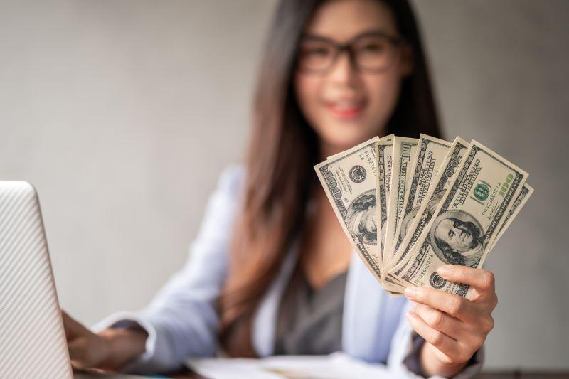 Woman on laptop holding cash