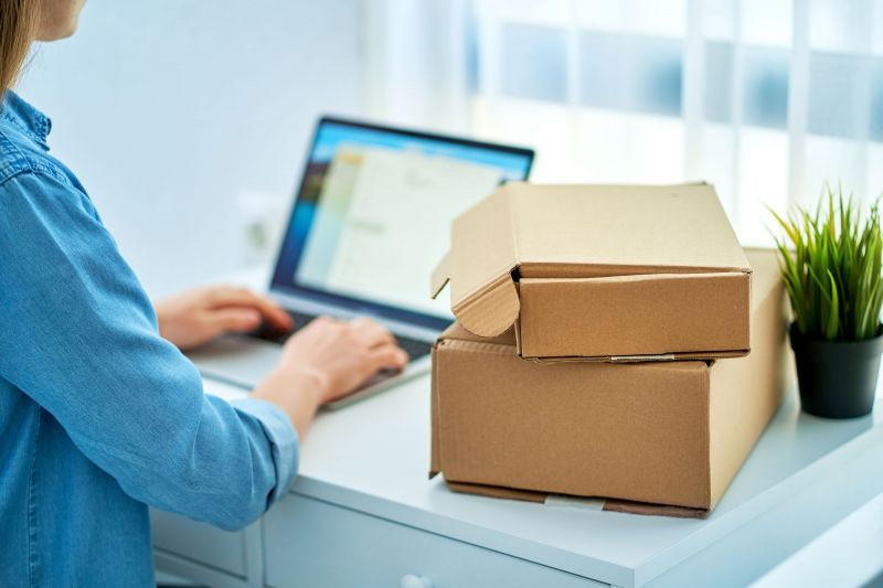 Woman on laptop next to pile of parcels