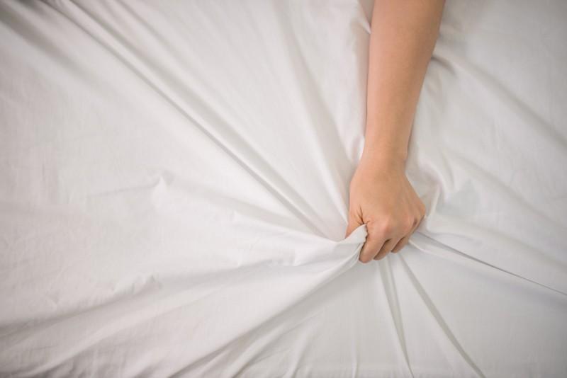Woman hand grabbing sheets