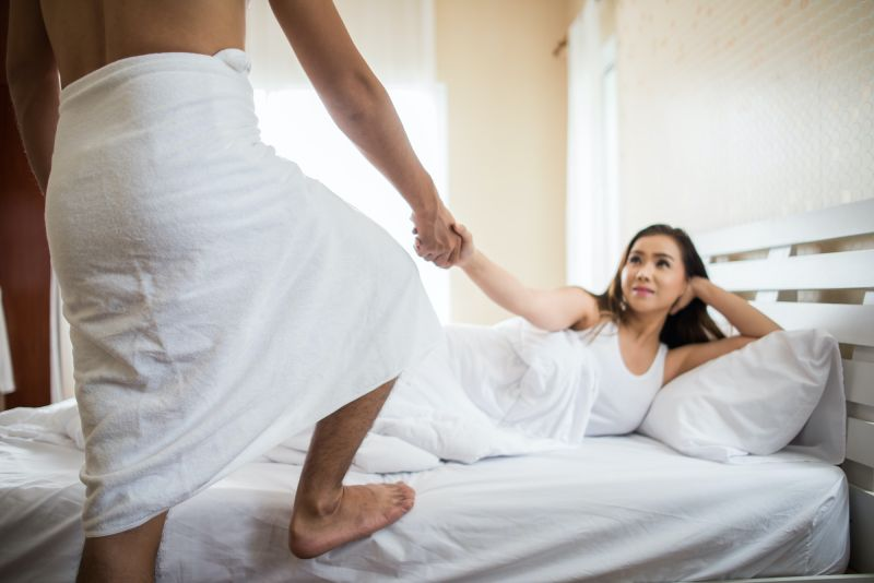 Woman pulling man into bed with her