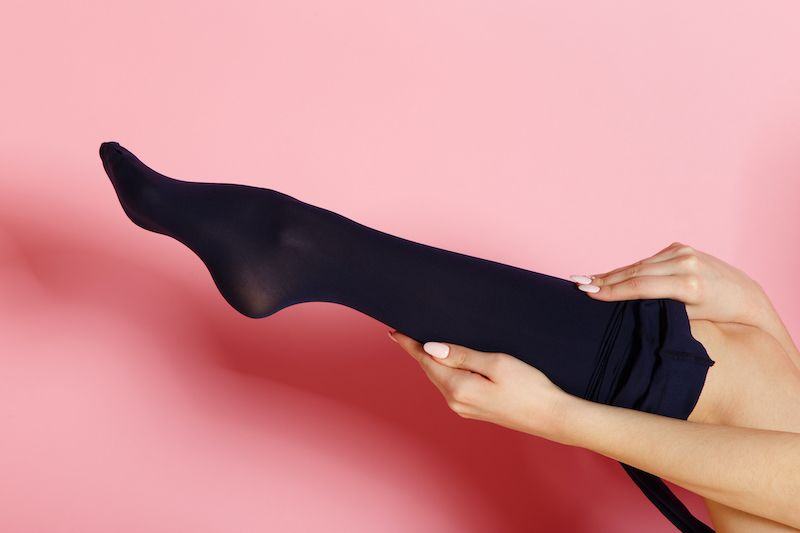 Woman pulling up black pantyhose