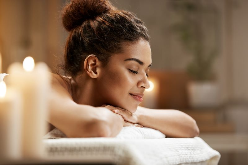 Woman relaxing in spa with candles