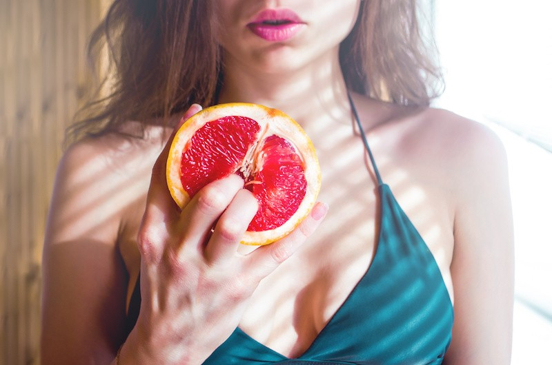 Woman grabbing pomegranate in a sexy posture