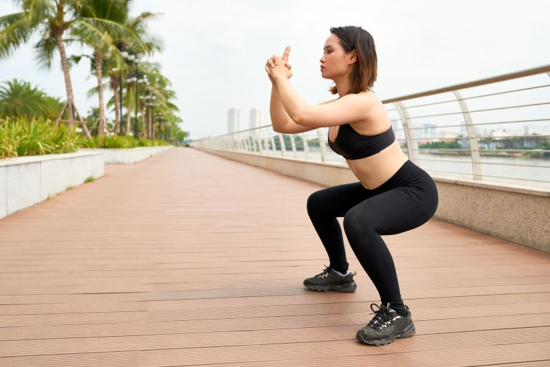 Woman squatting outside