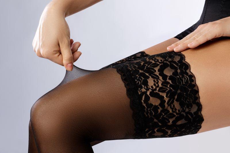 Woman touching stockings on leg