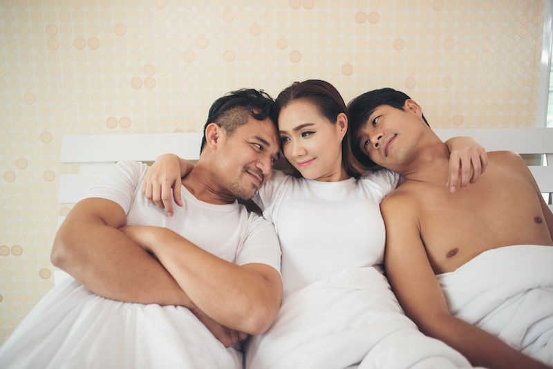 Woman with two men in bed