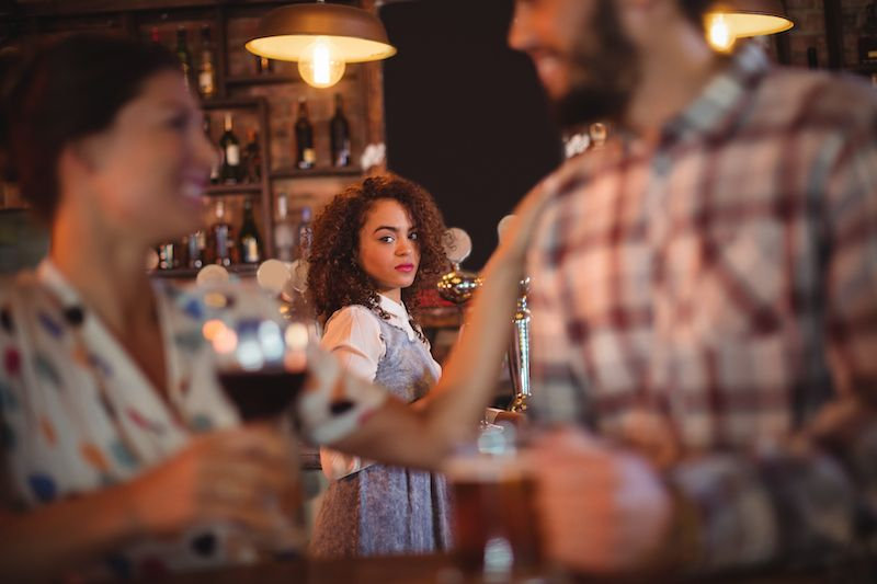 Woman looking jealous watching a couple across the room