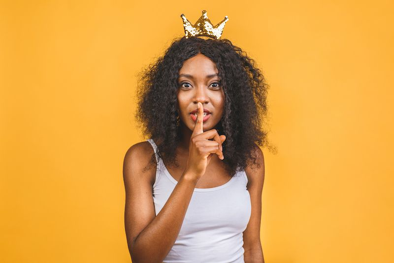 Woman wearing a crown making shh gesture