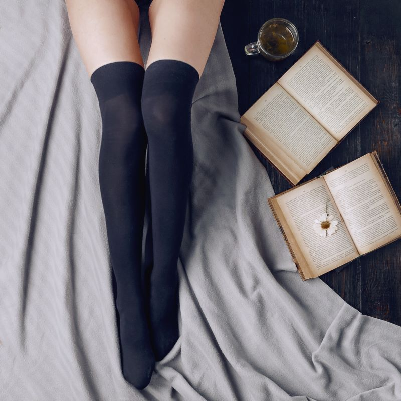 Woman's legs next to erotic books