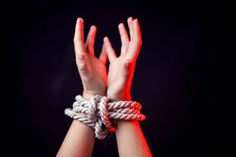 Woman with hands bound in rope