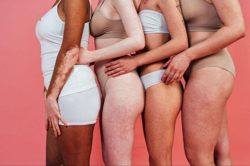Women hugging in underwear on pink background