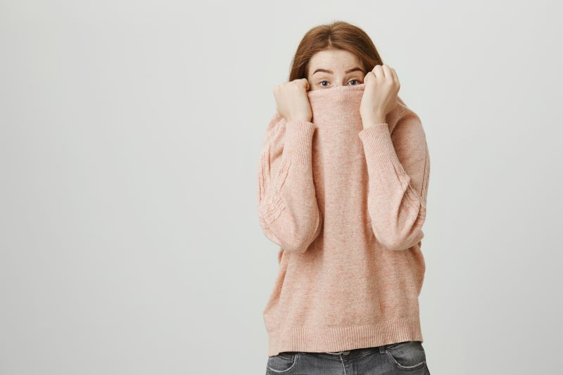 Woman hiding her face in a pink jumper