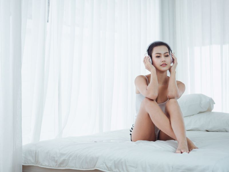 Woman listening to headphones in bed