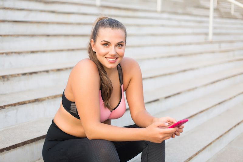 Woman in sports clothing sitting on stairs and holding her phone