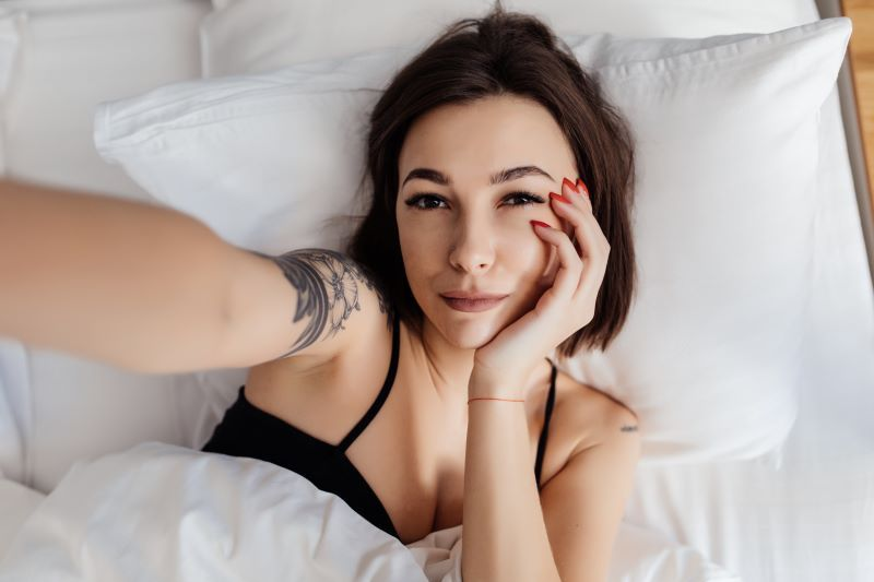 Woman taking selfie in bed