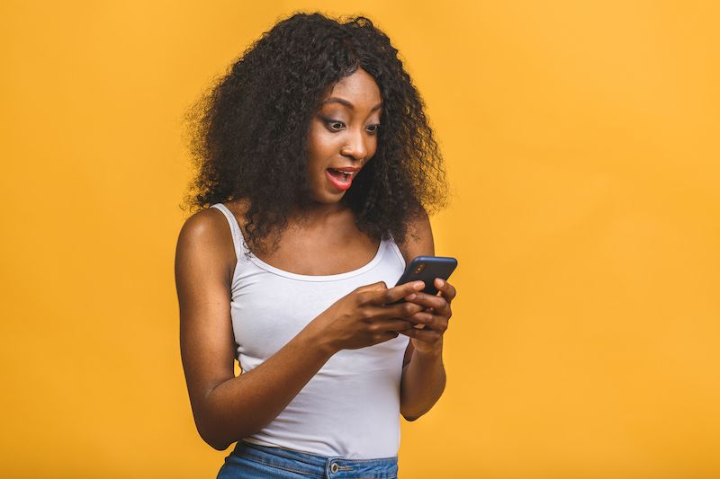 Young woman texting looking excited