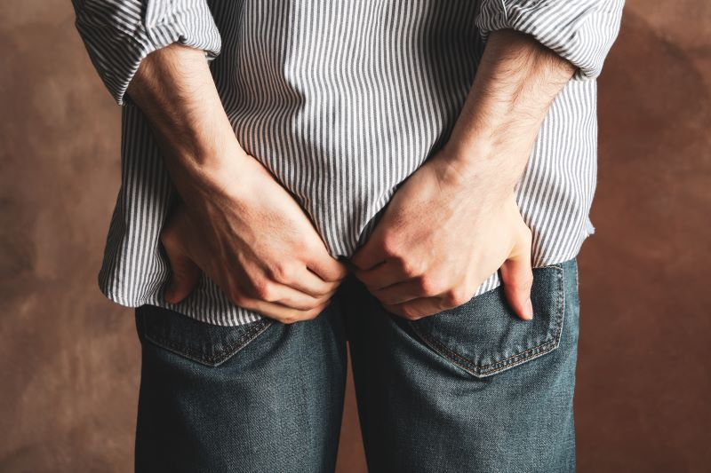 Man holding his butt through jeans
