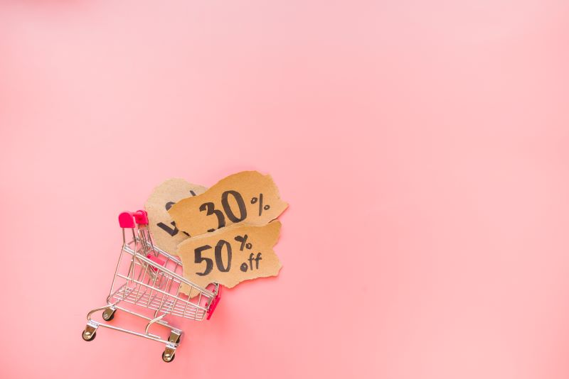 Mini shopping trolley on pink background sale concept