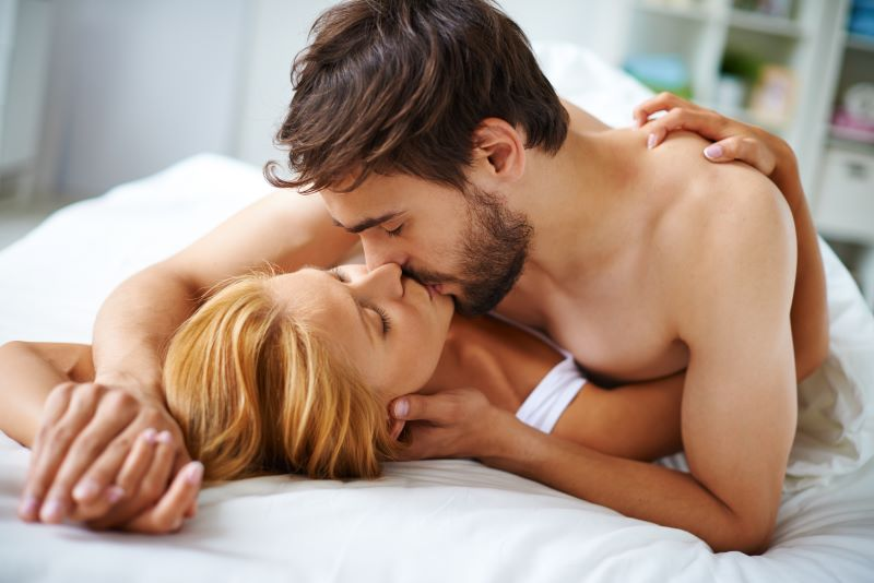 Sensual couple kissing in bed